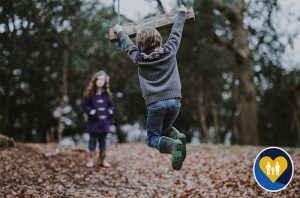 children jumping in leaves