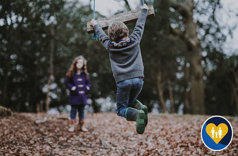 children jumping in leaves
