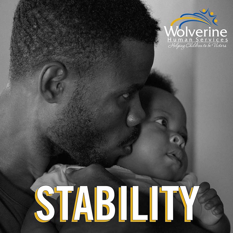 """ma holding baby with word """"stability"""" overlaid"""